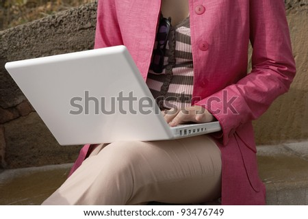 Close up of a young woman using a laptop computer outdoors. - stock photo