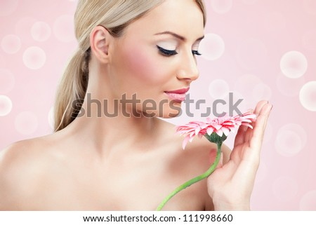 Close-up of a young woman with red flower - stock photo