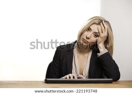 Close up of a young women's sad face. Her head rests in her hand as she sits at her keyboard. - stock photo