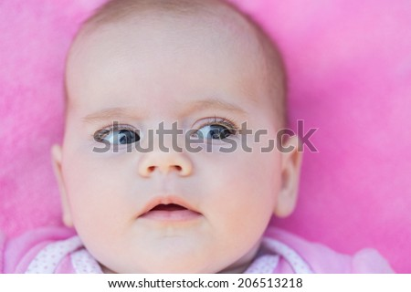 close up of adorable baby face in pink back ground