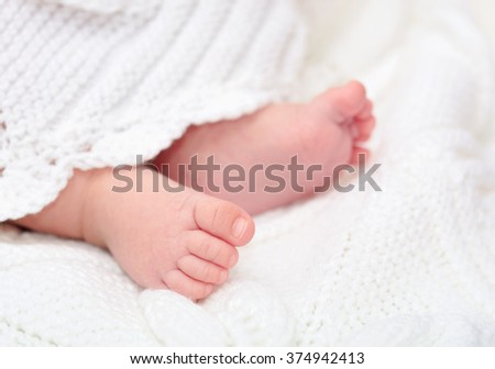Close up of adorable baby feet on blanket, focus on one foot