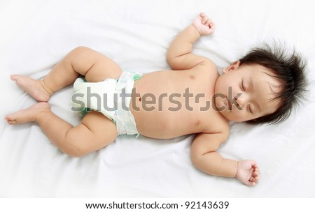 Close up of adorable little baby laying in the bed. - stock photo