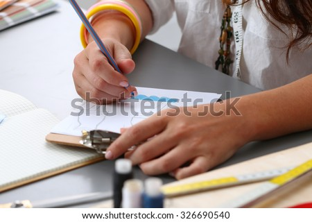 Close-up of adult female dressmaker drawing some clothing design - stock photo