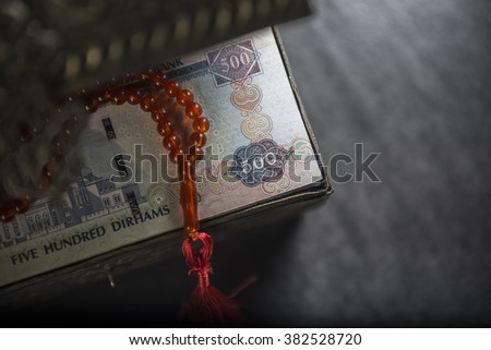 Close up of AED 500 notes in a vintage treasury box with islamic rosary. View from top. - stock photo