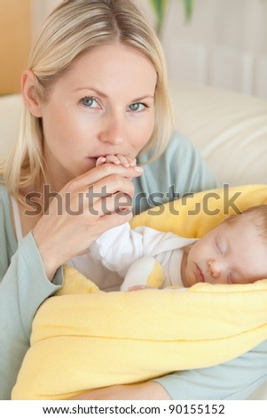Close up of affectionate young mother kissing her baby's hand - stock photo