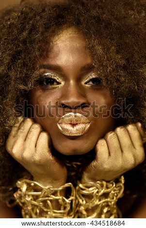 Close up of african american model wearing gold accessoaries, makeup and curly hair making kiss lips for camera - stock photo