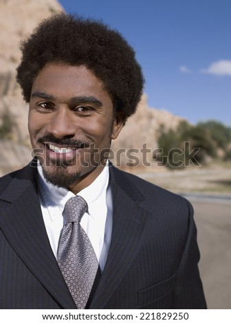 Close up of African businessman smiling - stock photo