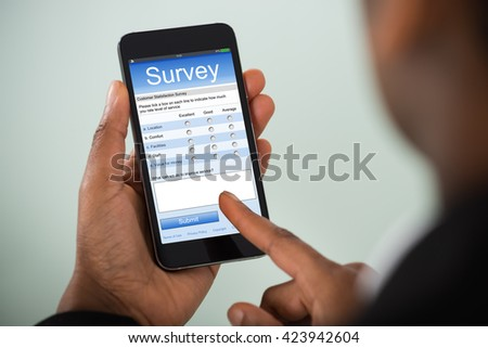 Close-up Of African Businesswoman Filling Online Survey On Mobile Phone
