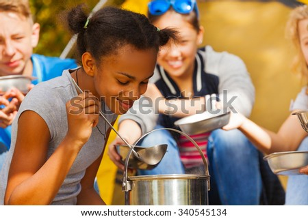 Close-up of African girl cooking soup at campsite - stock photo