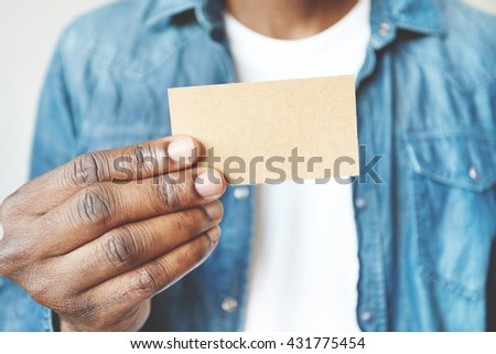 Close up of African man's hands holding business card with copy space for your text or advertising content. Film effect. Black male in white T-shirt and denim jacket showing blank card at the camera - stock photo