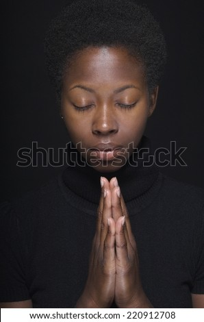 Close up of African woman praying - stock photo
