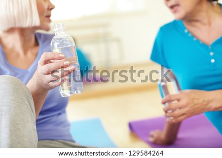 Close-up of aged women holding bottles of water and interacting in sport club - stock photo