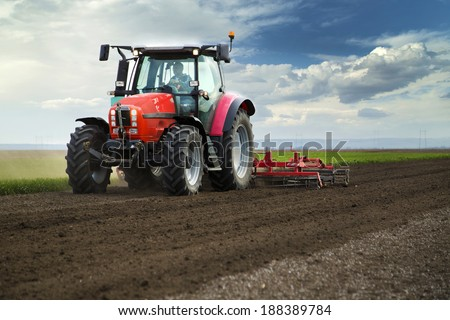 Close-up of agriculture red tractor cultivating field over blue sky - stock photo