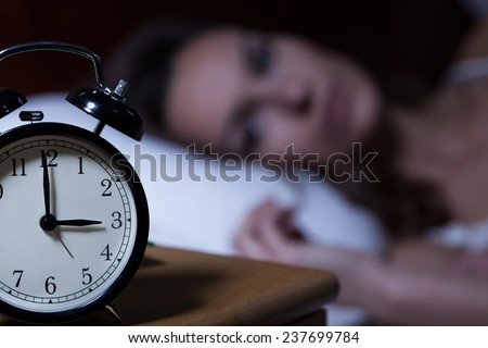 Close-up of alarm clock on night table - stock photo