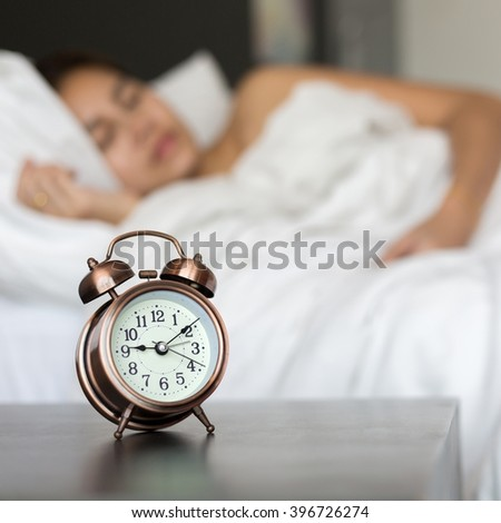 Close up of alarm clock on table and woman sleeping in background.