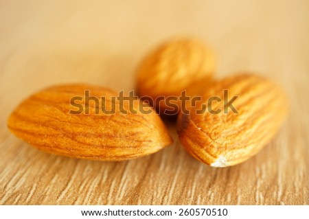 Close up of almonds on wood - stock photo