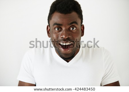 Close up of amazed young African American man in white blank T-shirt, having fun indoor, looking at the camera with excited expression, astonished with sale prices. Human face expressions and emotions - stock photo
