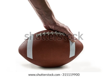 Close-up of American football player holding ball against white background - stock photo