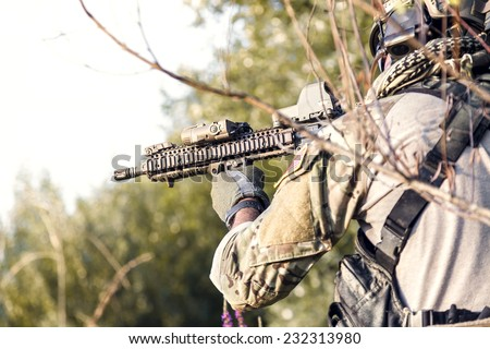 Close up of American Soldier aiming his rifle on the bushes - stock photo