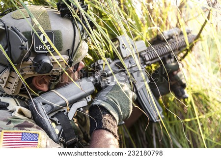 Close up of American Soldier aiming his rifle on the grass - stock photo