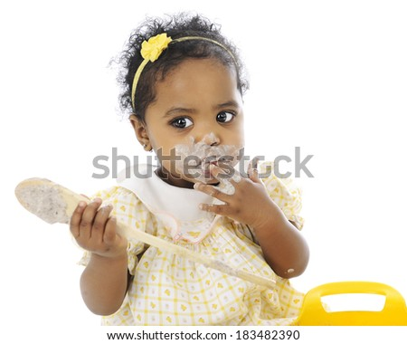 Close-up of an adorable baby girl sitting with a wooden spoon in her hand and a pudding-mess around her mouth.  On a white background.