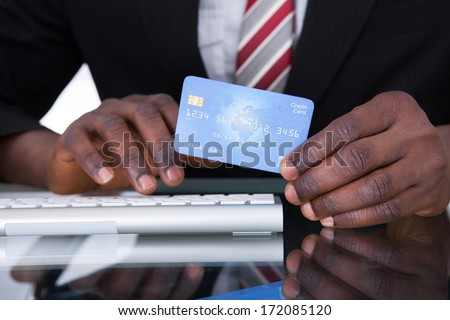 Close-up Of An African Businessperson Holding Credit Card - stock photo