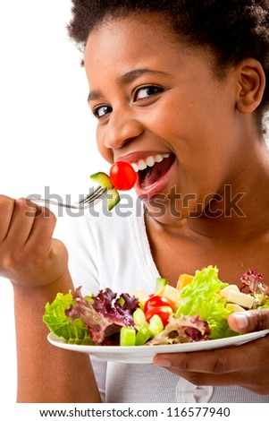 Close up of an African woman eating a salad on an isolated background - stock photo
