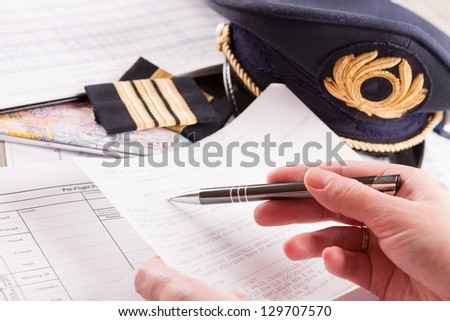 Close up of an airplane pilot hand filling in an flight plan and reading METAR with equipment including hat, epaulettes and other documents in background - stock photo