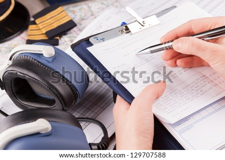 Close up of an airplane pilot hand filling in an pre-fligh checklist and holding weather forecast with equipment including hat, epaulettes and other documents in background - stock photo