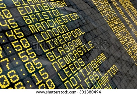 Close-up of an airport departure board to United Kingdom cities destinations, with environment reflection.Part of a series.