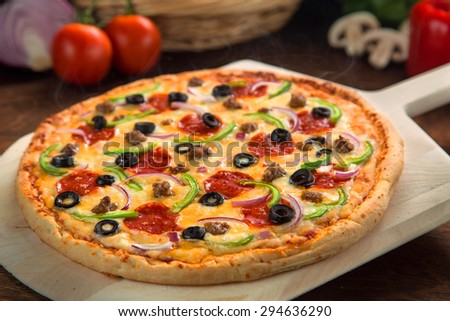 Close up of an amazing just baked supreme pizza made from garden ingredients by best chef - stock photo