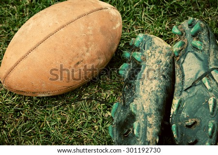 close up of an american football and sports shoes covered with mud - stock photo