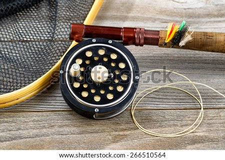 Close up of an antique fly fishing reel, rod, landing net and artificial flies on rustic wood. Layout in horizontal format. - stock photo