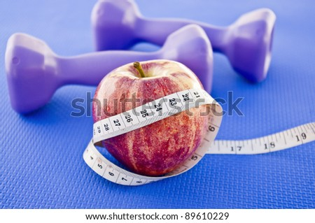 Close up of an apple with a measuring tape and dumbbells