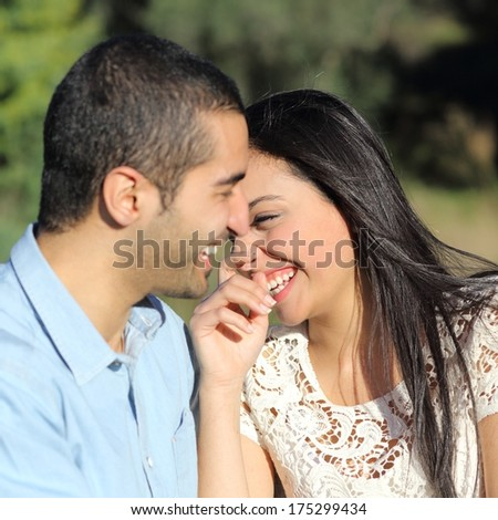 Close up of an arab casual couple flirting and laughing happy in a park - stock photo