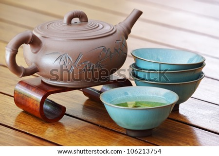 Close up of an asian tea set on a wooden surface. - stock photo