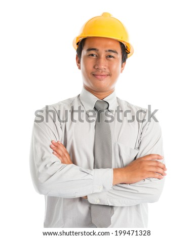 Close-up of an Asian young man wearing a hardhat smiling and looking at camera, arms crossed standing isolated on white background. - stock photo