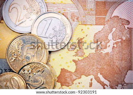Close-up of an assortment of Euro coins on a Euro bill background with a map of Europe.