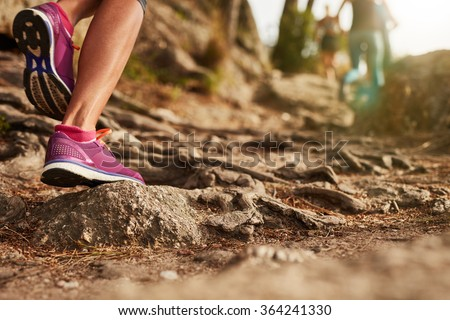 Close up of an athlete's feet wearing sports shoes on a challenging dirt track. Trail running workout on rocky terrain outdoors. - stock photo