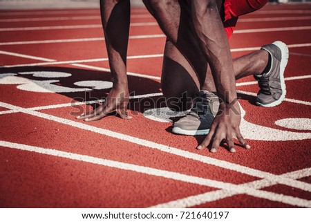 Close-up of an athlete's hand and foot plan push off a track with numbers in the stadium