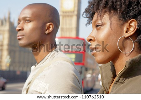 Close up of an attractive black tourist couple walking past Big Ben while visiting London city on vacation.