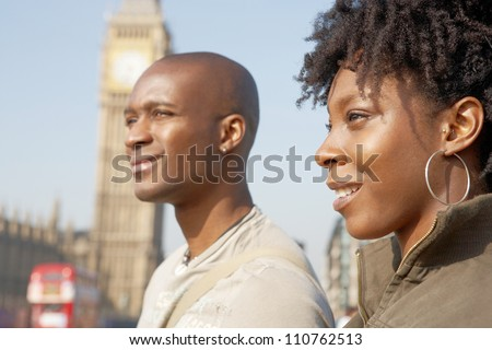 Close up of an attractive black tourist couple walking past Big Ben while visiting London city on vacation, smiling.