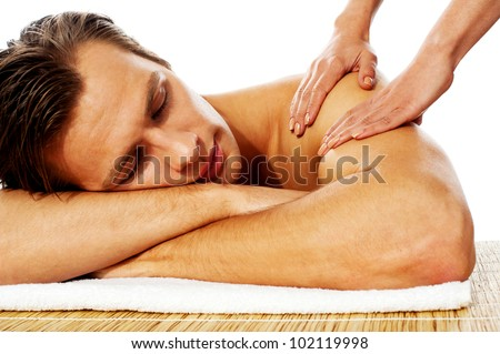 Close-up of an attractive man enjoying a back massage in a spa center - stock photo