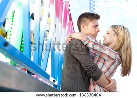 Close up of an attractive young couple hugging while visiting a funfair amusement park with rides, being romantic and smiling. - stock photo