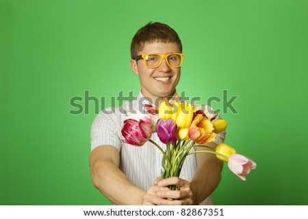 Close-up of an attractive young man in shirt bow tie and glasses holding a bouquet of tulips. Nerd - stock photo