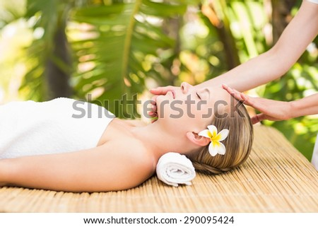 Close up of an attractive young woman receiving facial massage at spa center - stock photo