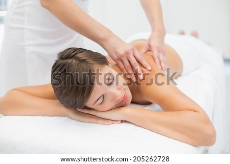 Close up of an attractive young woman receiving shoulder massage at spa center - stock photo
