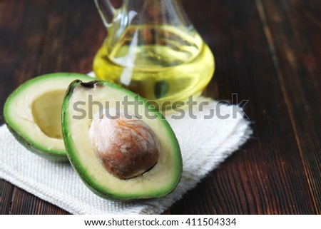 Close-up of an avocado and avocado oil on wooden table.