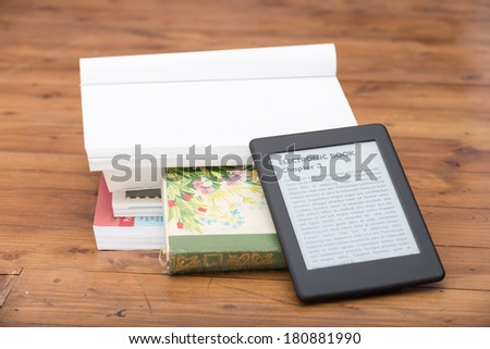 """Close Up of an ebook reader leaning over some traditional books on the floor. Everything is leaning on a vintage lovely parquet. The text on the ebook reader is an """"lorem ipsum"""" - stock photo"""