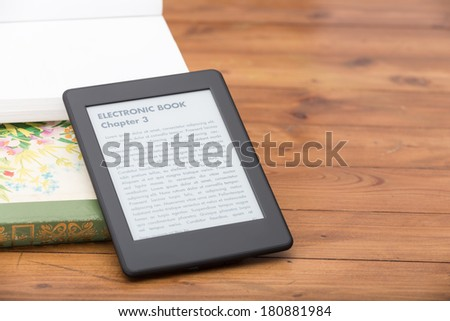 """Close Up of an ebook reader leaning over some traditional books on the side. Everything is leaning on a vintage lovely parquet. The text on the ebook reader is an """"lorem ipsum"""" - stock photo"""